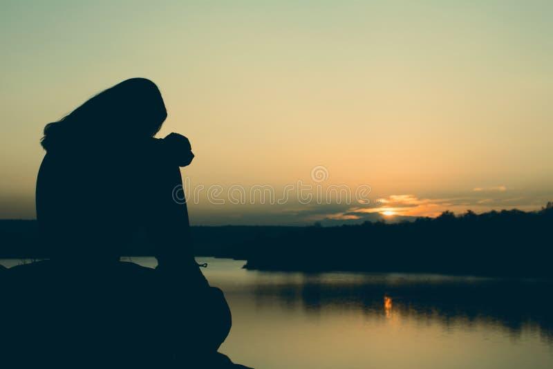 Schattenbild der besorgten Frau sitzend auf dem Felsen stockbild