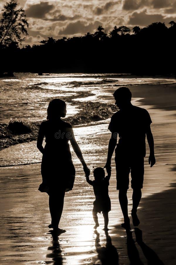 Schattenbild der Familie auf dem Strand am Sonnenuntergang lizenzfreie stockfotos