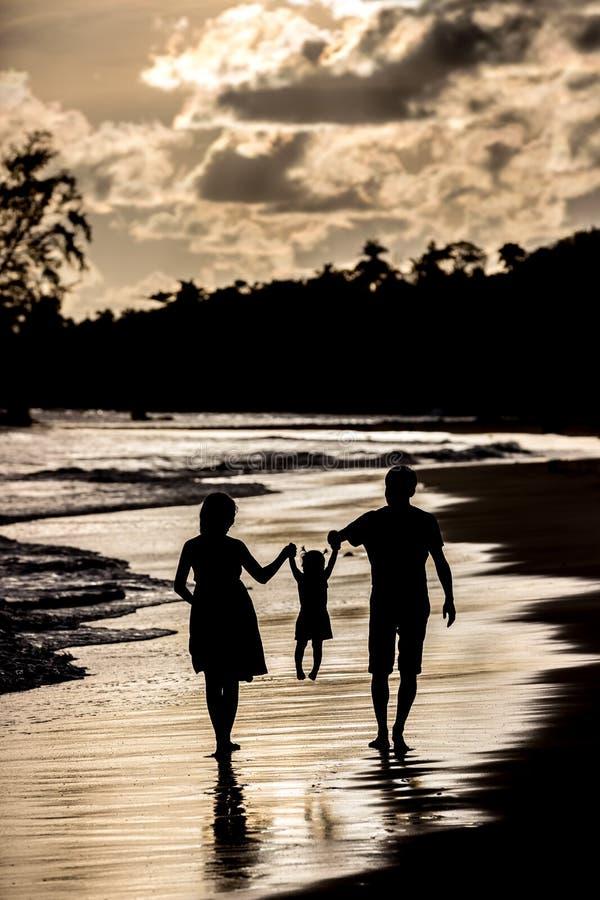 Schattenbild der Familie auf dem Strand am Sonnenuntergang stockbild