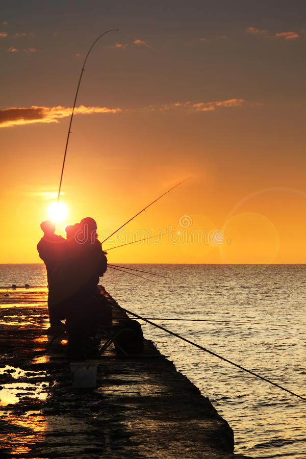 Schattenbild der Fischer lizenzfreie stockfotografie
