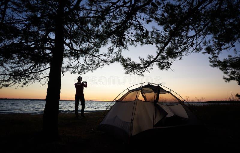 Schattenbild der Frau auf Seeufer nahe touristischem Zelt mit Fotokamera, Foto machend stockbilder