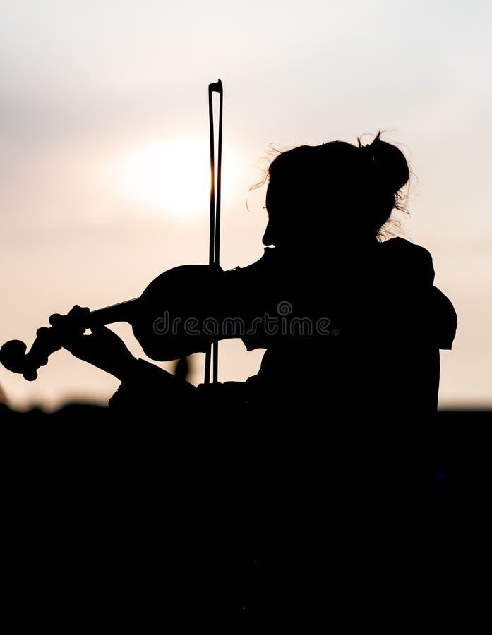 Schattenbild der Frau die Violine während des Sonnenuntergangs gegen das sonnen- eingelassene Prag spielend stockbild