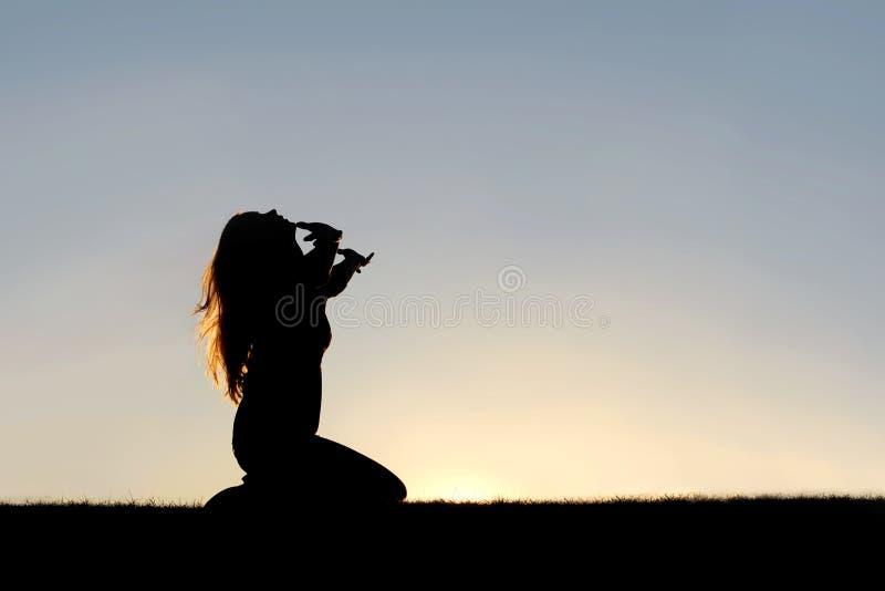 Schattenbild der Frau kniend im Gebet und in der Auslieferung lizenzfreies stockfoto