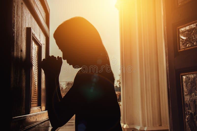 Schattenbild der Frau kniend und in der modernen Kirche an der Sonne betend stockfotos