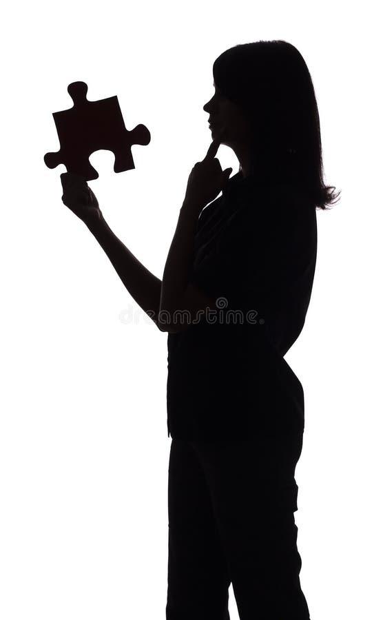 Schattenbild der Frau mit Puzzlespiel stockfotos