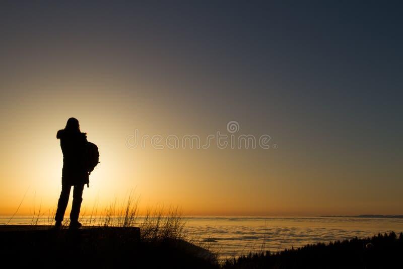 Schattenbild der Frau stehend im Sonnenuntergang lizenzfreie stockfotografie