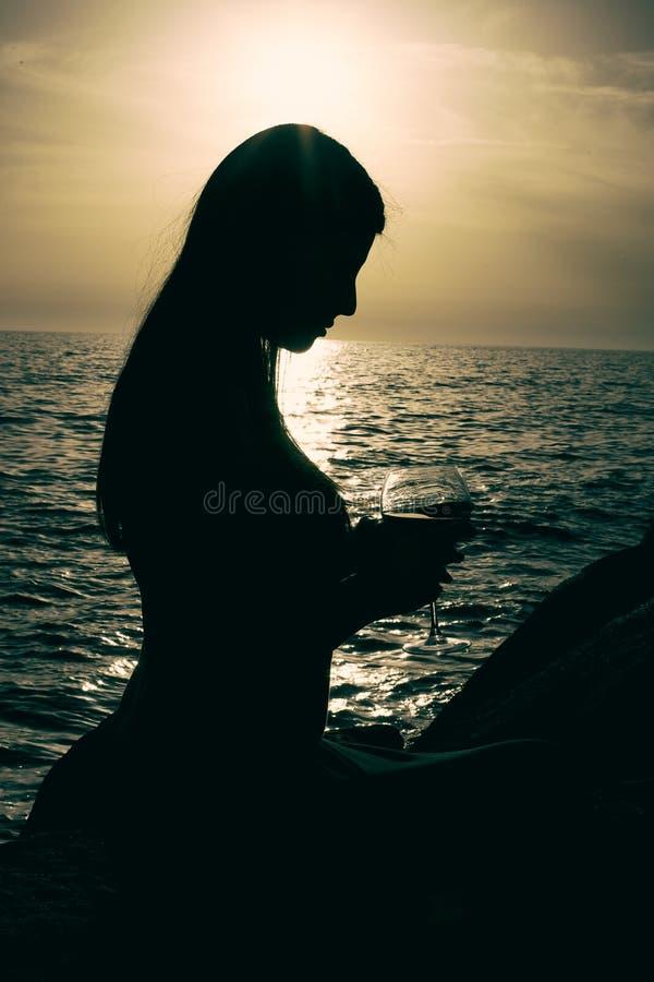 Schattenbild der Frau vor Sonnenuntergang und des Ozeans, der Glas Wein hält stockbilder