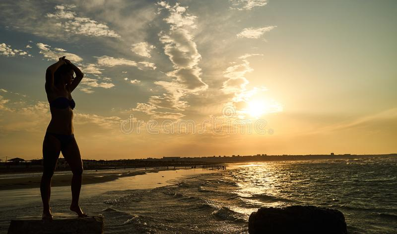 Schattenbild der freien Frau bei Sonnenuntergang auf dem Strand lizenzfreie stockbilder