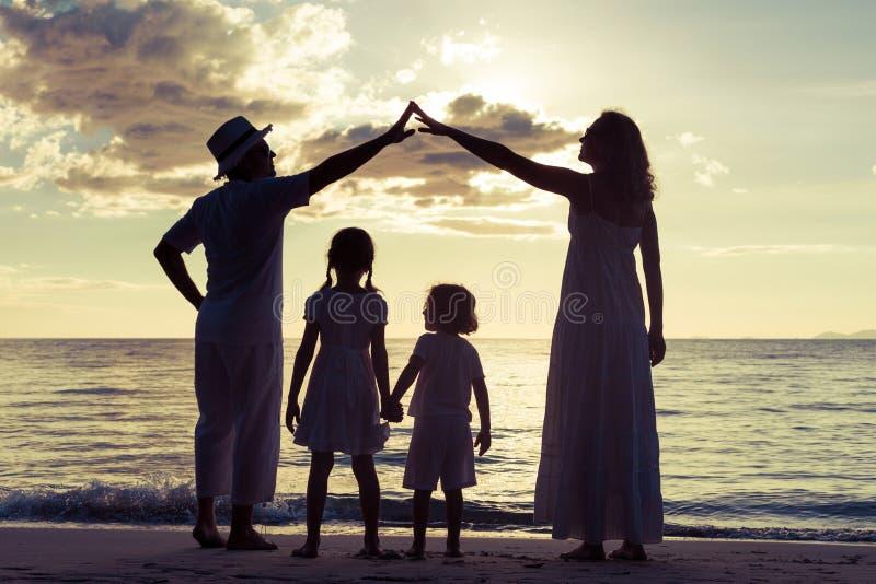 Schattenbild der glücklichen Familie das, die auf dem Strand am sunse spielt stockbild