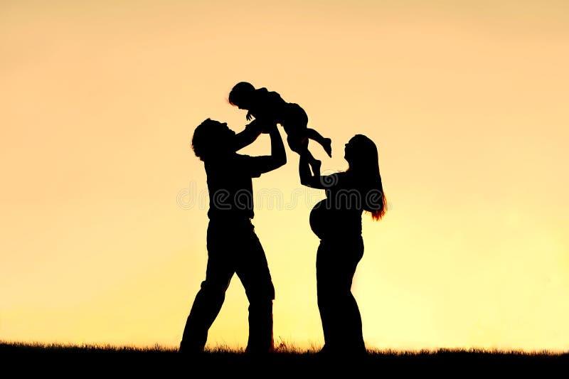 Schattenbild der glücklichen Familie Schwangerschaft feiernd lizenzfreie stockfotografie