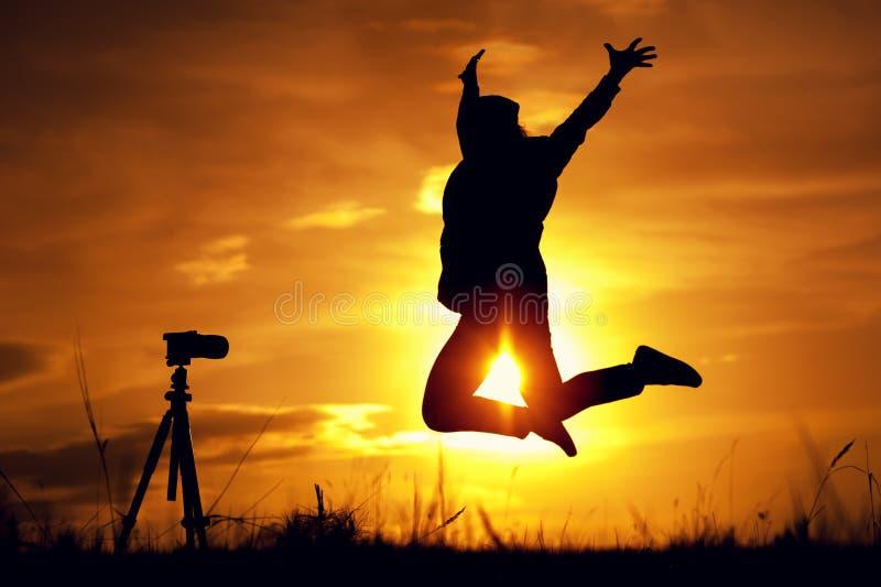 Schattenbild der glücklichen Frau fotografierend stockfoto