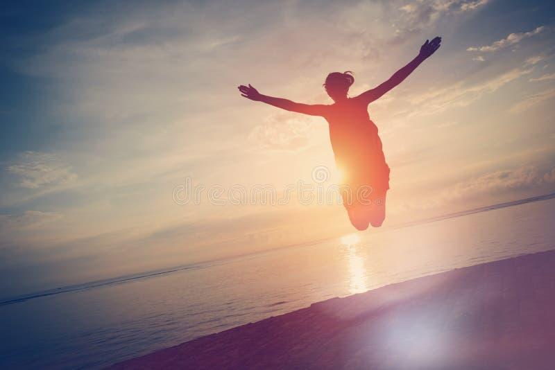Schattenbild der glücklichen Frau springend nahe Ozean bei Sonnenuntergang stockfotografie
