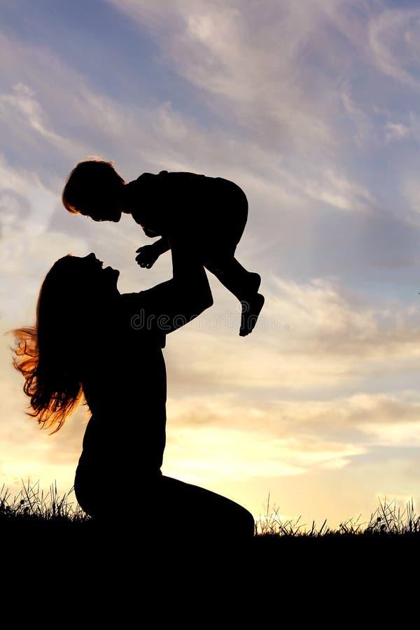 Schattenbild der glücklichen Mutter draußen spielend mit Baby lizenzfreie stockfotografie