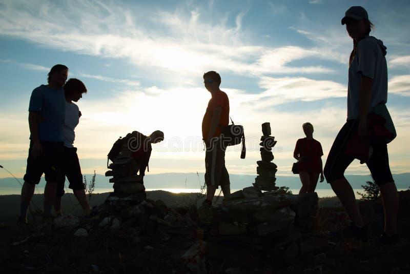 Schattenbild der Gruppe von Personen oben des Berges lizenzfreie stockfotografie