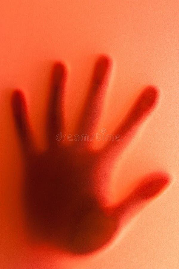 Schattenbild der Hand auf rotem Hintergrund. lizenzfreie stockfotografie