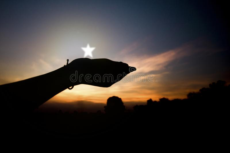 Schattenbild der Hand um Stern bitten und halten lizenzfreies stockbild