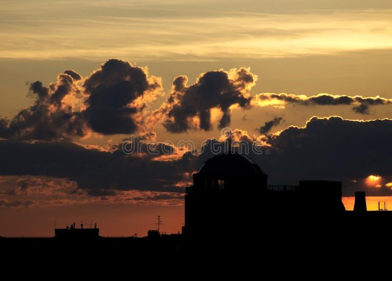 Schattenbild der Haube des Gebäudes gegen den Himmel mit den verschiedenen und merkwürdigen Wolken stockfotografie