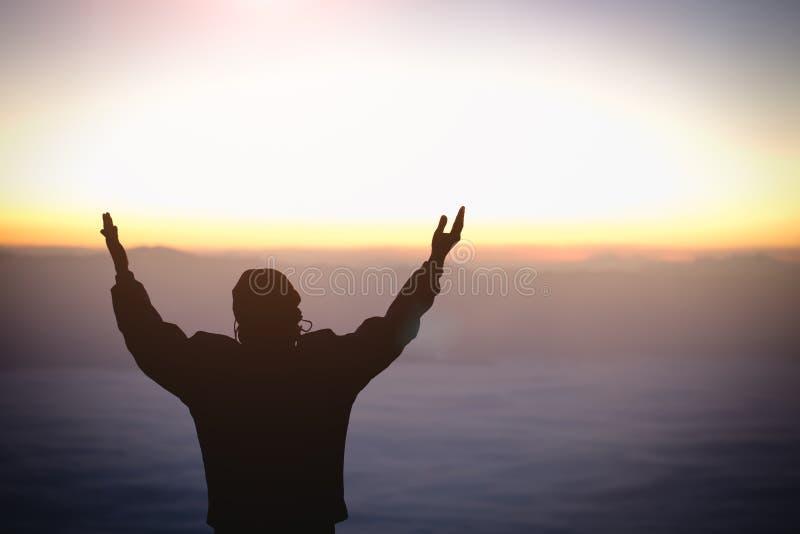 Schattenbild der junge menschliche Handoffenen Palme herauf Anbetung und des Betens zum Gott bei Sonnenaufgang, Christian Religio stockfotos