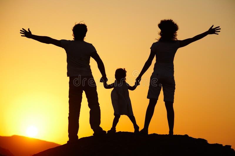 Schattenbild der jungen Familie auf Sonnenuntergang lizenzfreie stockfotografie