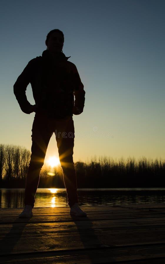 Schattenbild der jungen Frau bei Sonnenuntergang stockfotografie