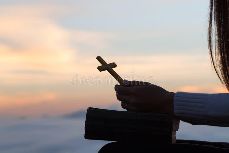 Schattenbild der jungen Frau betend mit Kreuzen und Bibeln bei Sonnenaufgang, Christian Religions-Konzepthintergrund lizenzfreie stockfotografie