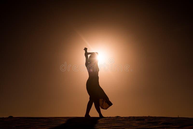 Schattenbild der jungen Frau mit langem Rocktanzen auf evokative und überzeugte Art auf Wüstendüne bei Sonnenuntergang mit Sonnen lizenzfreies stockfoto