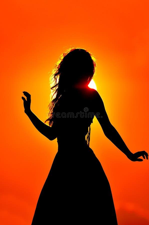 Schattenbild der jungen Frau am Sonnenuntergang stockfotos
