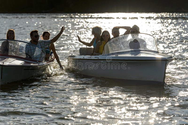 Schattenbild der jungen Freunde in den Motorbooten stockbilder