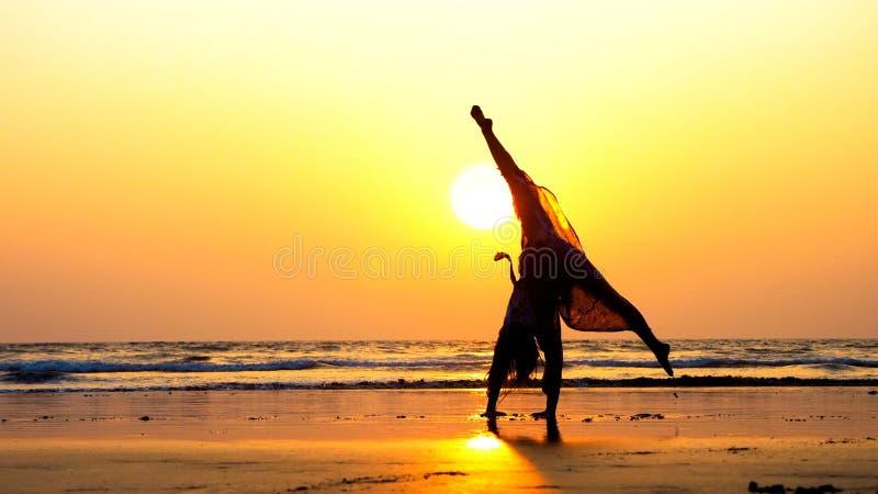 Schattenbild der jungen Turnerfrau, die Handspring auf sandigem Strand bei Sonnenuntergang tut stockbild