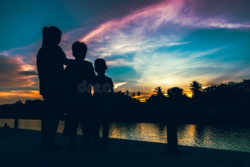 Schattenbild der Mutter mit Sohn und die Tochter, die Ansicht an genießt, rive lizenzfreie stockfotografie