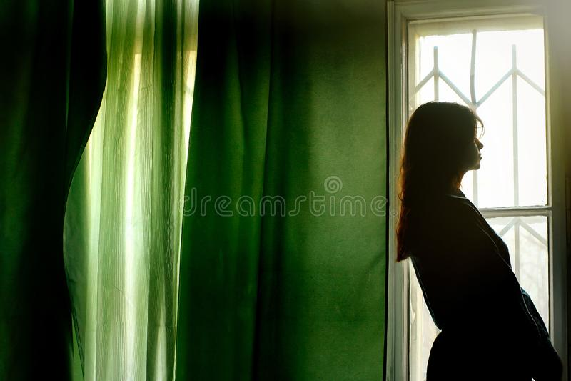 Schattenbild der Schönheit stehend an den grünen Vorhängen und am Klo lizenzfreie stockfotografie