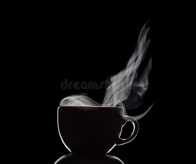 Schattenbild der Schale mit Dampf vom heißen Getränk lokalisiert auf Schwarzem lizenzfreies stockbild