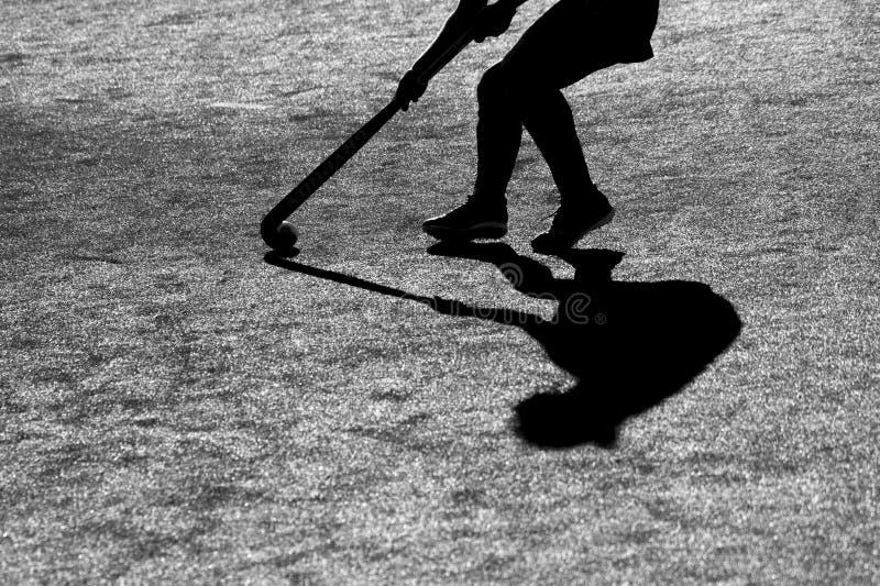 Schattenbild Der Schatten von Spielern eines Hockeys läuft mit einem Hockeyschläger auf einem Hockeyfeld stockfoto
