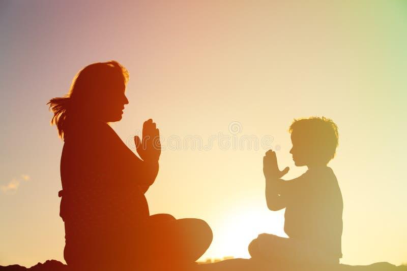Schattenbild der schwangeren Mutter und des Sohns, die Yoga auf Strand tut stockbilder