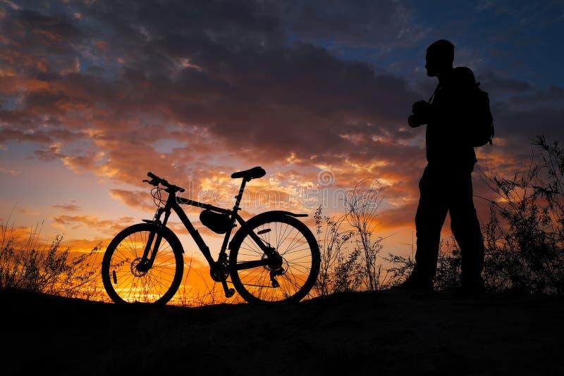 Schattenbild der Sportperson radfahrend auf die Wiese lizenzfreies stockfoto