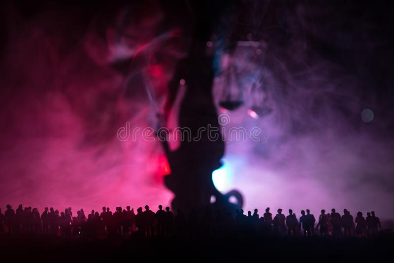 Schattenbild der unscharfen riesigen Damengerechtigkeitsstatue mit Klinge und der Skala, die hinter Menge nachts mit nebeligem Fe stockfotos