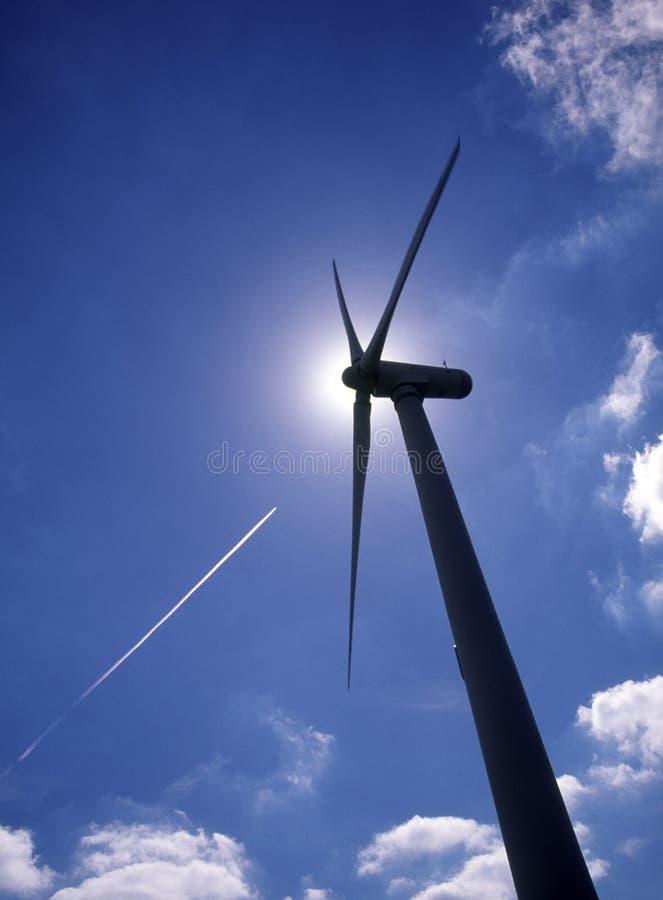 Schattenbild der Windkraftanlage mit Düsenflugzeug-Dampfspur lizenzfreies stockbild