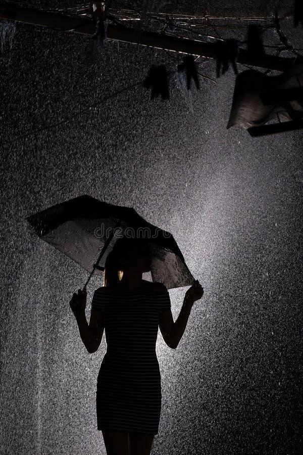 Schattenbild der Zahl eines jungen Mädchens mit einem Regenschirm im Regen, ein Profil der jungen Frau stockbilder