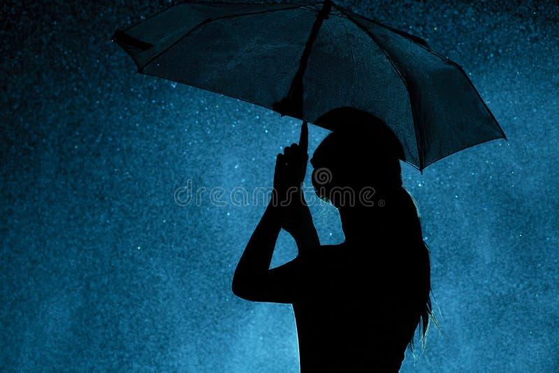 Schattenbild der Zahl eines jungen Mädchens mit einem Regenschirm im Regen, eine junge Frau ist zu den Wassertropfen, Konzeptwett stockfotos