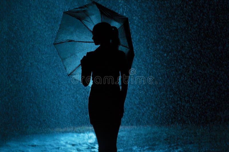 Schattenbild der Zahl eines jungen Mädchens mit einem Regenschirm im Regen, eine junge Frau ist zu den Wassertropfen, Konzeptwett stockfoto