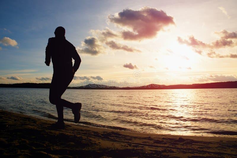Schattenbild des aktiven Mannes des Sports, der auf Strand bei klarem buntem Sonnenuntergang läuft und trainiert stockfotografie