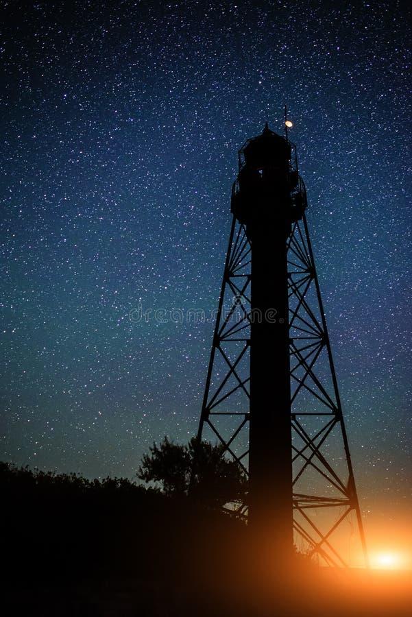 Schattenbild des alten Leuchtturmes und der Bäume vor dem hintergrund des sternenklaren Himmels mit Schein des Lichtes stockbilder