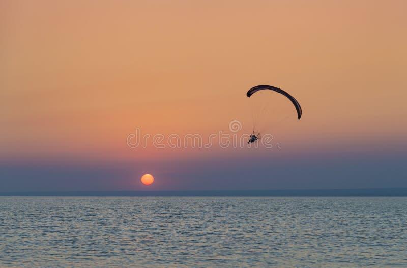 Schattenbild des angetriebenen hochfliegenden Fluges des Gleitschirms über dem Meer-aga lizenzfreie stockbilder