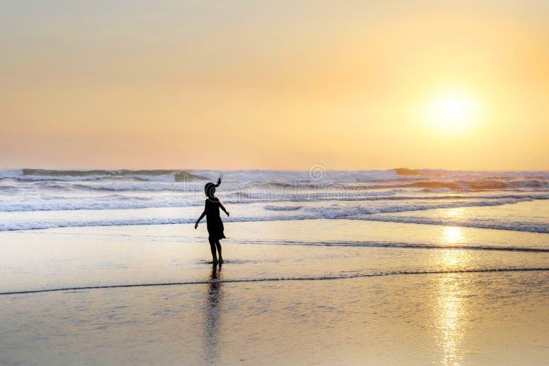 Schattenbild des anonymen weiblichen Kindes, das auf erstaunlichem schönem Wüstenstrand auf Sonnenuntergang mit einem orange Himm stockfoto