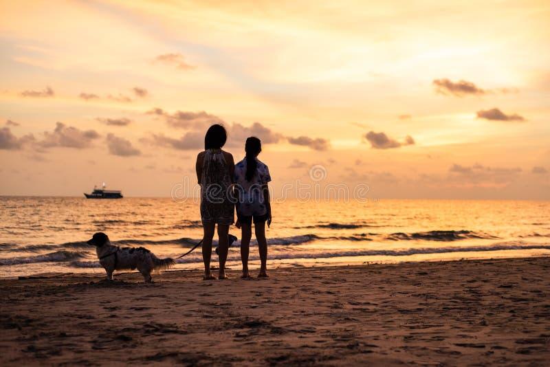 Schattenbild des asiatischen Mädchens auf dem Strand auf Sonnenuntergang stockbilder