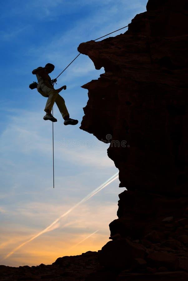 Schattenbild des Bergsteigers über schönem Sonnenuntergang stockfotos