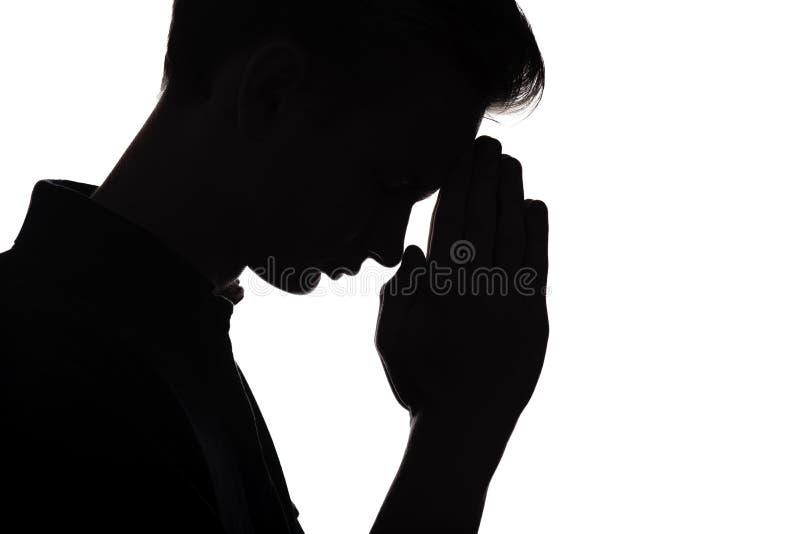 Schattenbild des Betens des jungen Mannes auf Weiß lokalisierte Hintergrund stockbild