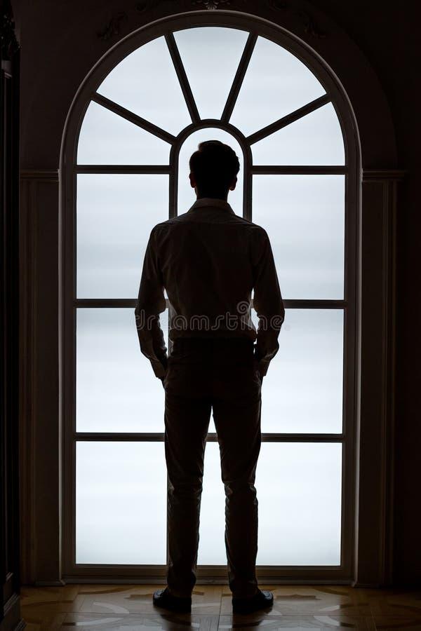 Schattenbild des Bräutigams auf dem Fensterhintergrund Das Konzept des Morgenbräutigams stockfotografie