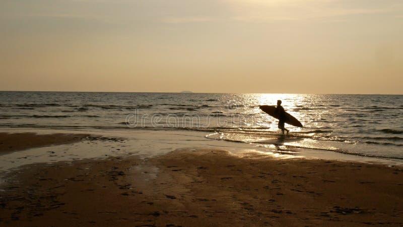 Schattenbild des Brandungsmannes mit dem Surfbrett, das auf Wasseroberfläche läuft stockfoto