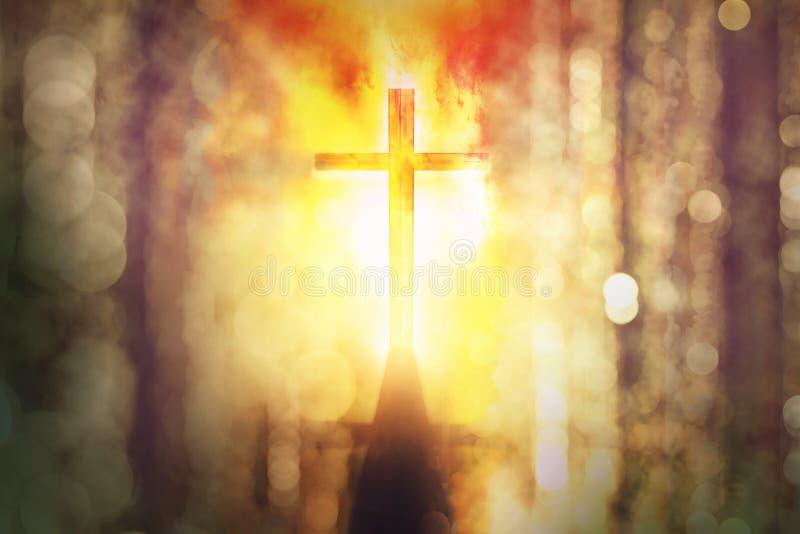 Schattenbild des brennenden Kreuzes mit Strahlen des Sonnenlichts lizenzfreies stockfoto